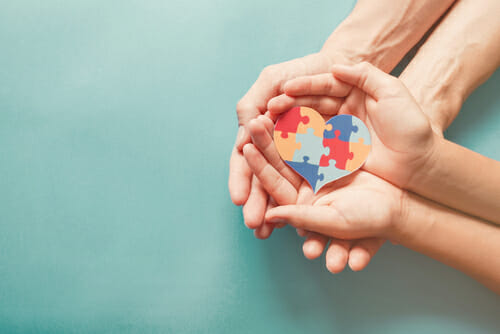 Image of hands holding a heart puzzle for our FAQ How is Autism Treated?