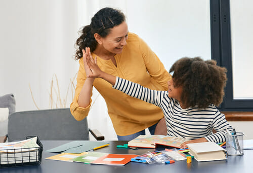 An image of a behavioral analyst giving a high five to a child she is working with for our article on behavioral managment planning.